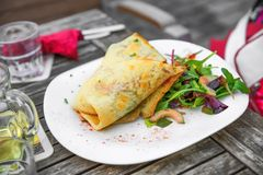 Stuffed tortilla wrap, rucola,carrot and cucumber on wooden table with wine. Tortilla wrap stuffed with goat cheese, beetroot, mushroom and dip, garnished with stock photos