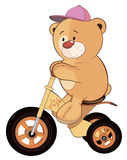 A stuffed toy bear cub and a children's tricycle cartoon Stock Photos