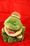 Stuffed Toy Frog On Red Background. Stuffed green gentleman frog with a bowtie and brown derby hat on a red background Royalty Free Stock Photo