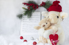 Stuffed toy lamb holding a small toy bear holding a heart. Horizontal christmas image of toy stuffed lamb holding small toy baby bear holding a red heart facing royalty free stock images