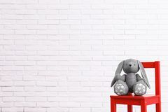 Stuffed toy rabbit on chair against white wall, space for text. Child room interior details. Stuffed toy rabbit on chair against white brick wall, space for text stock photography