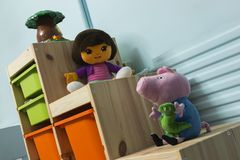 The Stuffed Toys. Kids playroom with toys Peppa Pig Dora The Explorer on wooden furniture stock photos