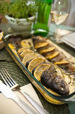 Stuffed trout with lemon dish. Delicious dish of trout fish stuffed with onion, basil and herbs, decorated with lemon Stock Photo