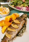 Stuffed trout with lemon dish. Delicious dish of trout fish stuffed with onion, basil and herbs, decorated with lemon Stock Photography