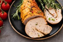 Stuffed turkey breast with baked vegetables and spices on a black background. Stuffed turkey breast with baked vegetables and spices against holiday background royalty free stock photo