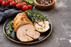 Stuffed turkey breast with baked vegetables and spices on a black background. Stuffed turkey breast with baked vegetables and spices against holiday background royalty free stock images