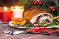 Stuffed turkey breast with baked vegetables and spices against holiday lights background. Stuffed turkey breast with baked vegetables and spices against holiday stock photo