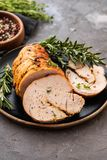 Stuffed turkey breast with baked vegetables and spices on a black background. Stuffed turkey breast with baked vegetables and spices against holiday background stock photo