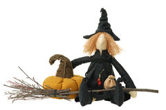 Stuffed witch toy with broom and pumpkin. Stuffed witch toy sitting with witch's broom and pumpkin. Isolated on white Stock Image