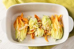 Stuffed zucchini or courgette blossoms in a casserole dish on a stock image