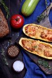Stuffed zucchini halves roasted with cheese. On a black cutting board royalty free stock photos