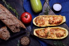 Stuffed zucchini halves roasted with cheese. On a black cutting board royalty free stock photo