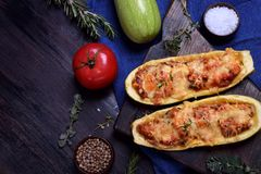 Stuffed zucchini halves roasted with cheese. On a black cutting board royalty free stock photography