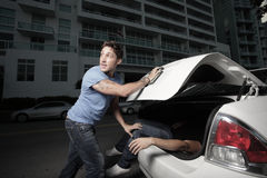 Stuffing a body in the trunk. Man stuffing a body in the trunk Stock Photography