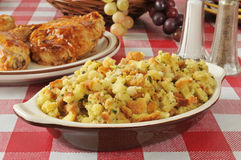 Stuffing and chicken. A bowl of corn bread stuffing with barbecued chicken in the background Stock Photos