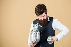 Stuffing some cash into his pockets. Bearded man hiding away cash holdings. Businessman taking cash money out of glass royalty free stock image