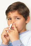 Stuffy nose and inhaler. Boy inhaled air passages due to colds and clogged nose Royalty Free Stock Image