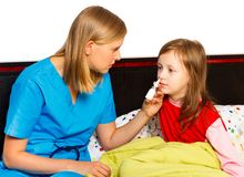 Stuffy Nose. Pediatrician administrating nasal spray for the stuffy nose of her patient Royalty Free Stock Photos