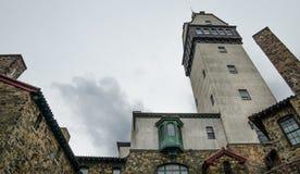 Stuga för stenvägg med tornet på mörk molnig dag Arkivbild