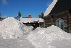 stuga utanför snowdrifts Royaltyfri Foto