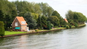 Stugahem längs flodshorelinen med träd och grönt gräs Royaltyfri Fotografi