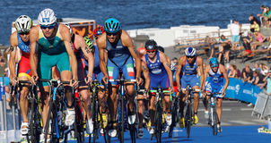 Stuggling, muscular triathlon competitors cycling uphill Stock Image