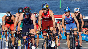 Stuggling, muscular triathlon competitors cycling uphill Royalty Free Stock Photo