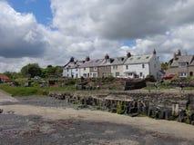 Stugor som förbiser den Craster hamnen Northumberland arkivfoto