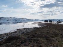 Stugor vid en djupfryst bergsjö Royaltyfri Bild