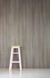 Stuhl auf Boden mit lamellenförmig angeordneter Wand Stockfotografie