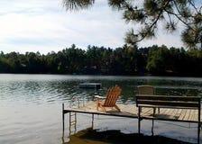 Stuhl auf einem Dock in einem See Stockbild