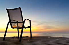 Stuhl auf einem Pier nahe dem Meer während des Sonnenaufgangs Lizenzfreies Stockfoto