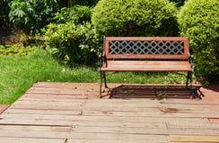 Stuhl auf hölzernem Patio des Hinterhofgartens, hölzerne Plattform im Freien Stockfotografie