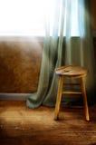 Stuhl durch Fenster Stockbild