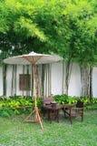 Stuhl eingestellt und Regenschirm im Garten Stockbild