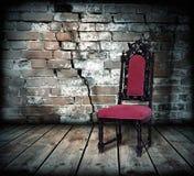 Stuhl gegen eine Backsteinmauer Stockbild