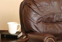 Stuhl mit Bibel und Becher stockbilder