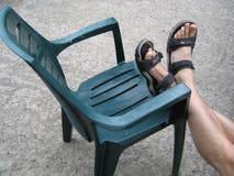 Stuhl mit Füßen auf ihm Lizenzfreie Stockbilder