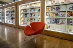 Stuhl mit mit den Zeitschriften im Hintergrund in der Bibliothek von Amsterdam Stockfotografie