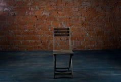 Stuhl und alte Backsteinmauer Lizenzfreies Stockfoto