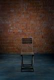 Stuhl und alte Backsteinmauer Lizenzfreie Stockbilder