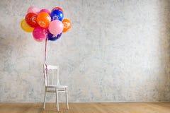 Stuhl und Ballone auf dem Bretterboden im Raum Stockbilder