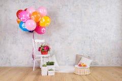 Stuhl und Ballone, Blumenkorb und Kuchen Stockbild