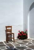 Stuhl und Pelargonien - Paros Stockbild