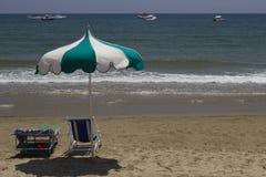 Stuhl und Regenschirm auf dem Strand Lizenzfreie Stockbilder