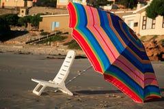 Stuhl und Regenschirm auf dem Strand am Sonnenuntergang Stockfotos