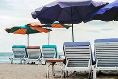 Stuhl und Sonnenschirme auf Strand mit blauem Ozean lizenzfreies stockfoto