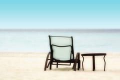 Stuhl und Tabelle auf dem Strand Stockfotografie