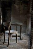 Stuhl und Tabelle in verlassenem Lager Stockfotos