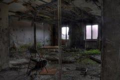 Stuhl und Tabelle in zerstörtem Raum Stockbild